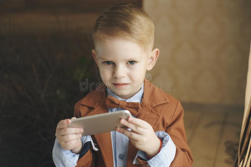 Leisure, children, technology, internet communication and people concept - smiling boy with smartphone texting message stock photo