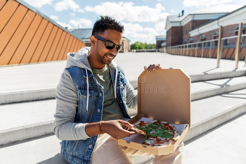 Indian man eating takeaway pizza on roof top. Leisure and fast food concept - indian man eating takeaway pizza on roof top stock photos