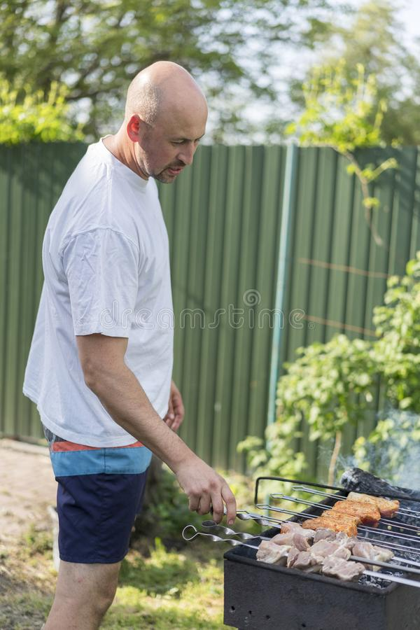 leisure, food, people and holidays concept - happy young man cooking meat on barbecue grill at outdoor summer party royalty free stock photography