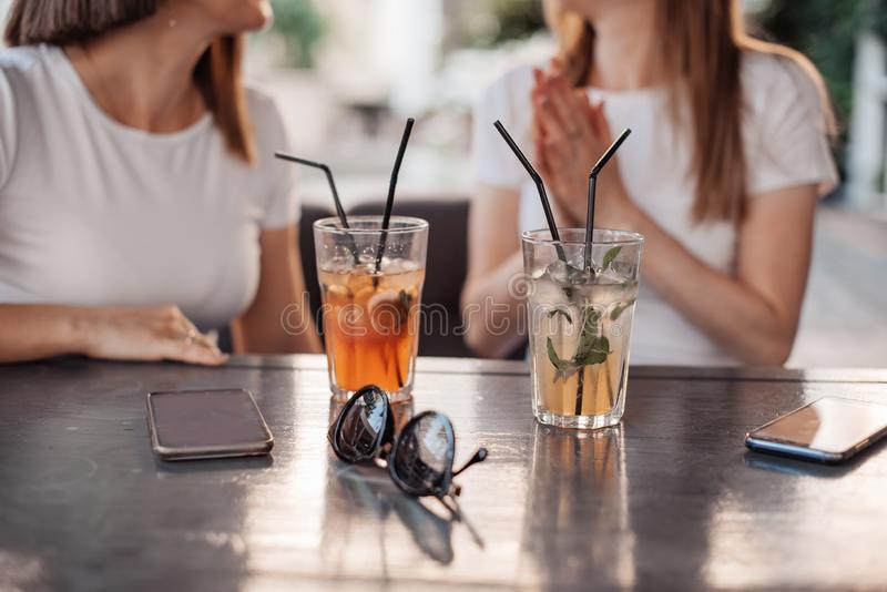Leisure, holidays, eating, people and food concept - happy friends having dinner at summer garden party and clinking drinks stock photography