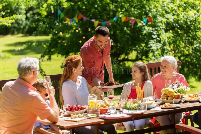 Happy family having dinner or summer garden party stock image