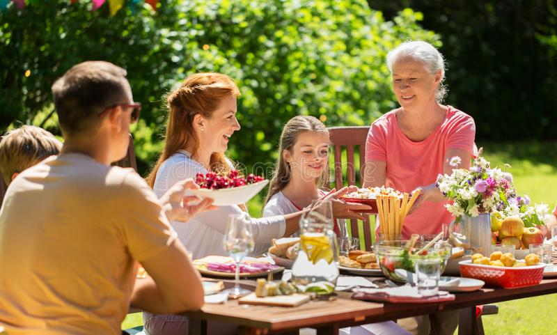 Happy family having dinner or summer garden party. Leisure, holidays and people concept - happy family having festive dinner or summer garden party stock photography