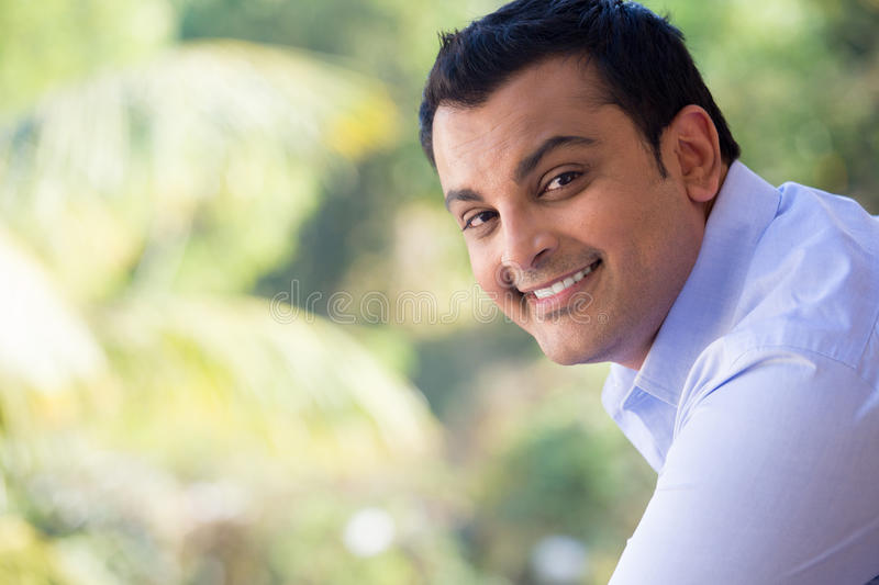 Leisure living. Closeup portrait of handsome happy young man in blue shirt standing outside on his balcony, isolated outdoors outside background with green trees stock photography