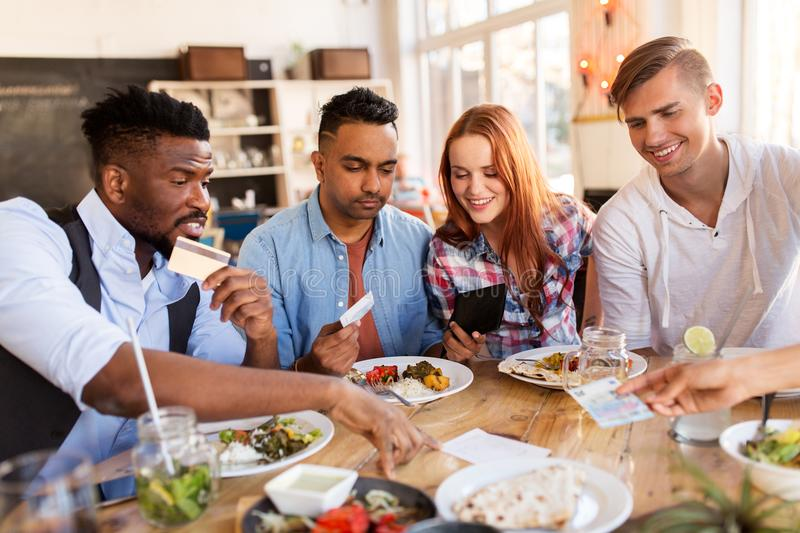 Happy friends with money paying bill at restaurant. Leisure, payment and people concept - happy friends with money and credit card paying bill for food at stock photography