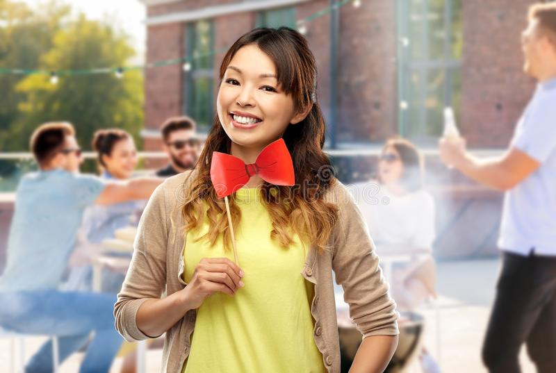 Happy asian woman with bow tie over rooftop party stock photos
