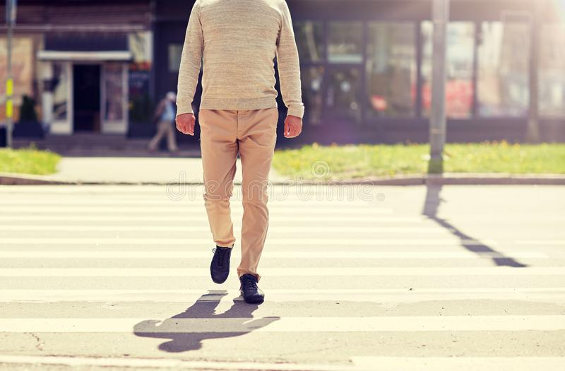 Senior man walking along city crosswalk stock photos