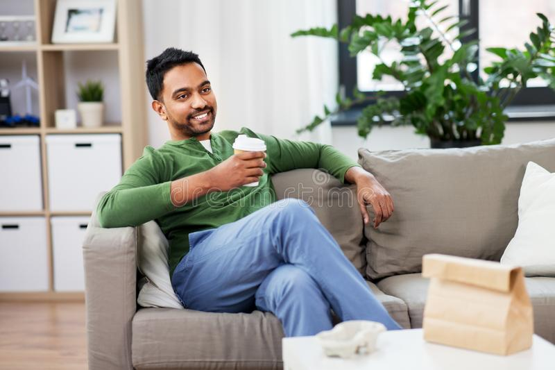Happy indian man drinking takeaway coffee at home. Leisure and people concept - smiling indian man drinking takeaway coffee at home royalty free stock images