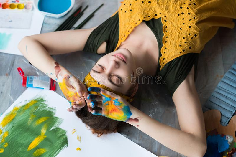 Leisure recreation artist floor hands paint. Leisure and recreation. Top view of peaceful female artist lying down on floor with her eyes closed, hands dirty stock image