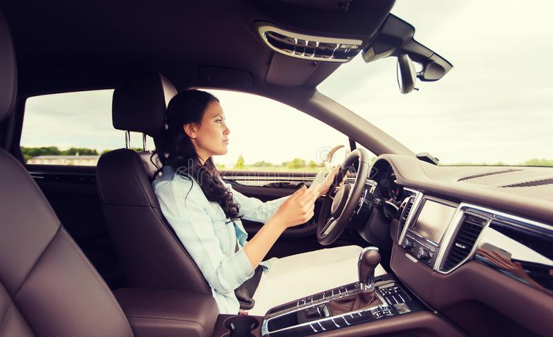 Happy woman driving car with smarhphone royalty free stock photo