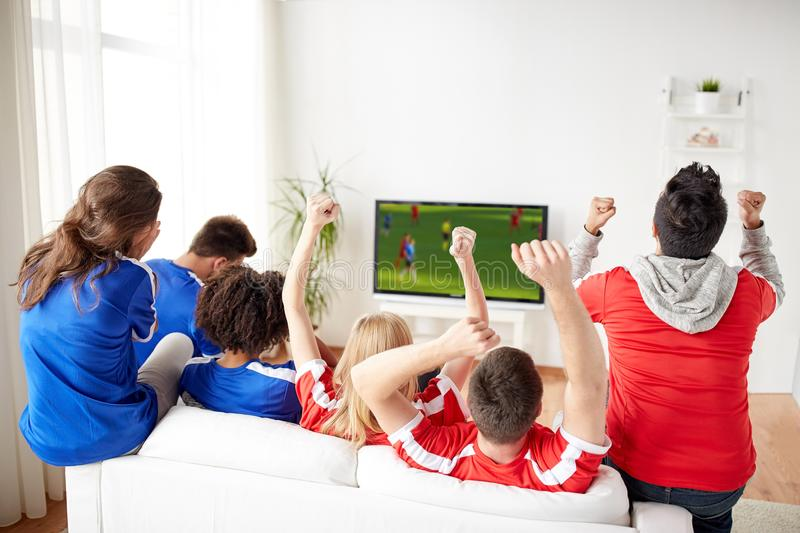 Friends or soccer fans watching game on tv at home. Leisure, sport and entertainment concept - happy friends or football fans watching soccer game on tv and stock photography