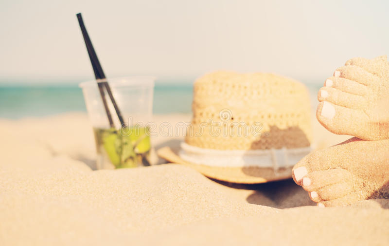 Leisure in summer - Beautiful of women feet, female legs on sandy beach with hat and mojito cocktail. Mojito cocktail on the royalty free stock photos