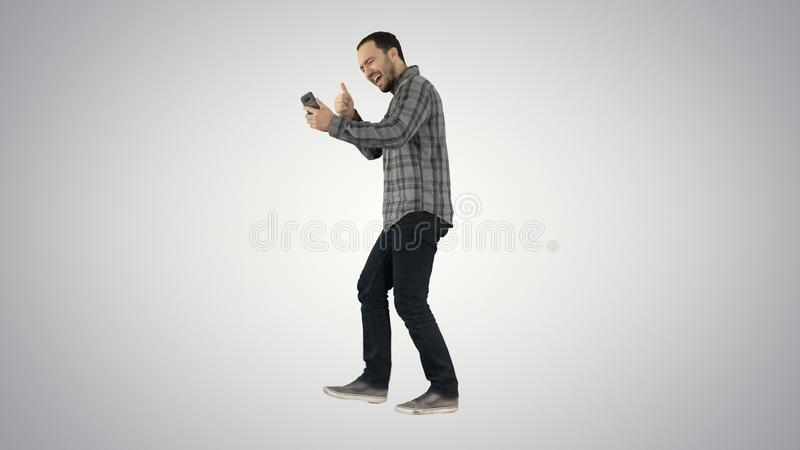 Leisure, technology, communication and people concept - young man using and calling on smartphone while walking on royalty free stock images