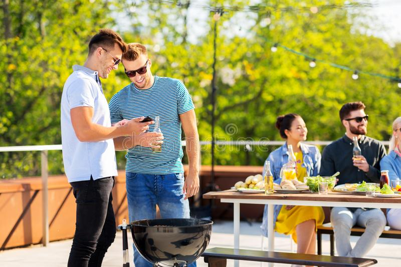 Happy friends grilling at bbq party on rooftop royalty free stock photography