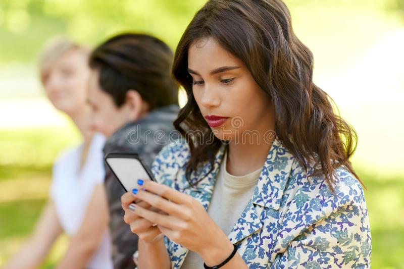 Woman using smartphone with friends at summer park stock photo