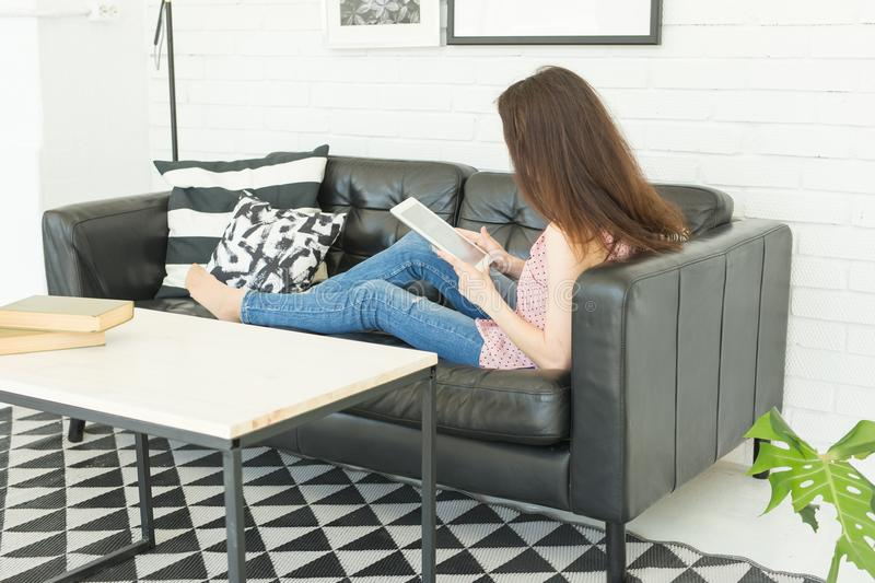 Leisure, technology and people concept - young brunette woman using tablet at home stock images