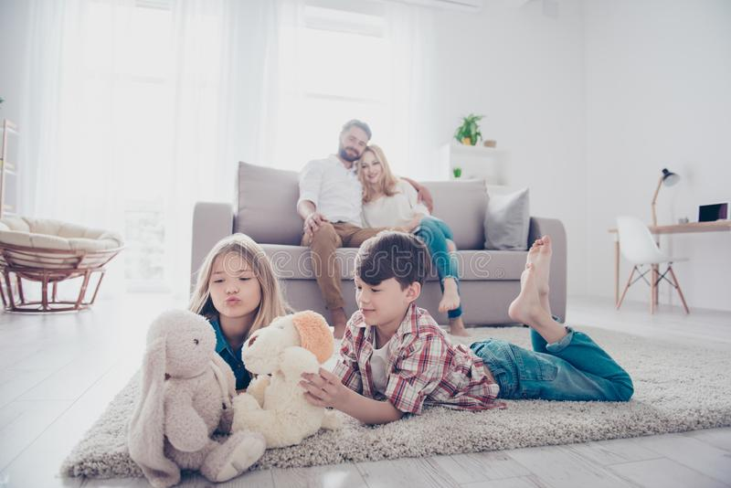 Leisure together. Happy family of four is enjoying at home, small kids are playing with toys, parents are on the sofa, hugging royalty free stock images