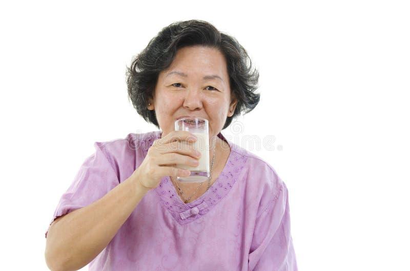 Leite bebendo da mulher sênior imagem de stock