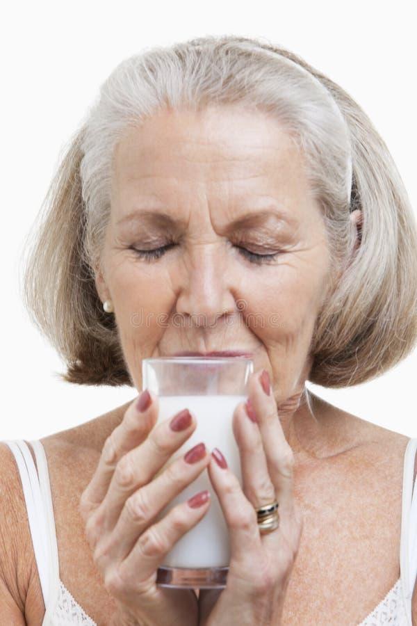 Leite bebendo da mulher superior contra o fundo branco foto de stock