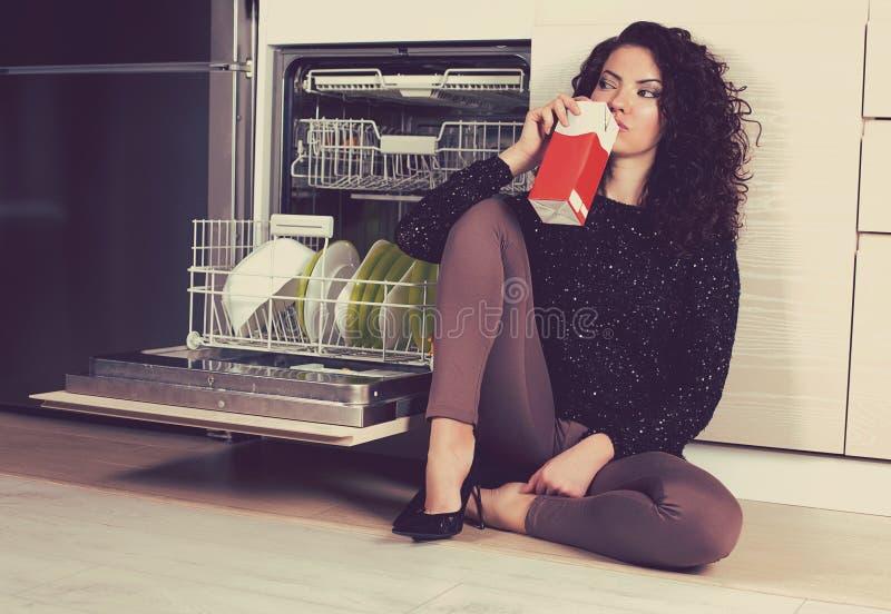 Leite bebendo da mulher triste na cozinha imagem de stock