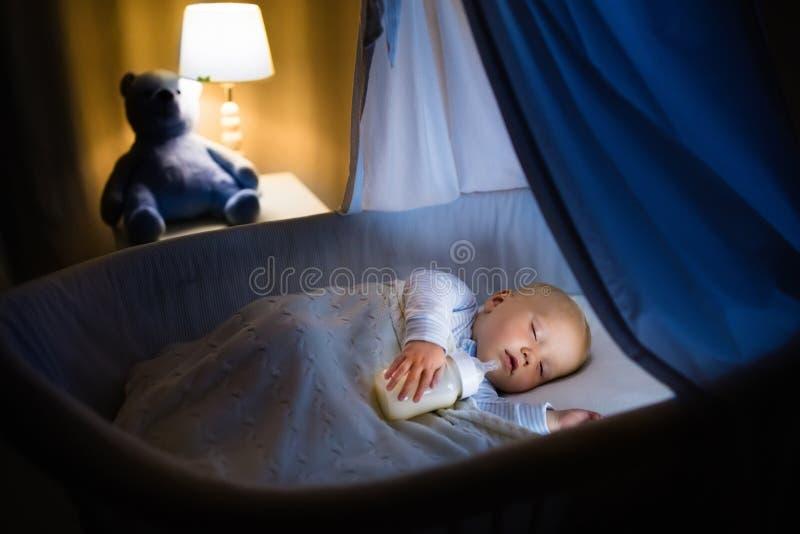 Leite bebendo do bebê na cama fotografia de stock