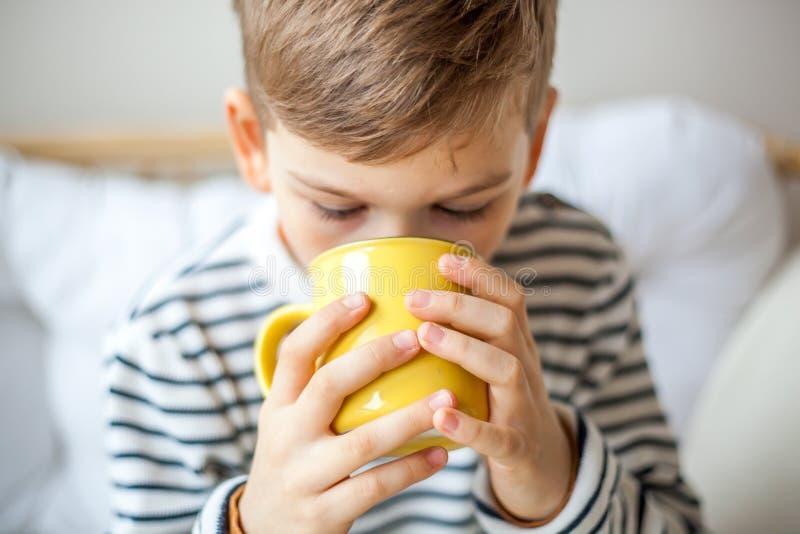Leite bebendo do rapaz pequeno bonito da caneca amarela imagens de stock royalty free