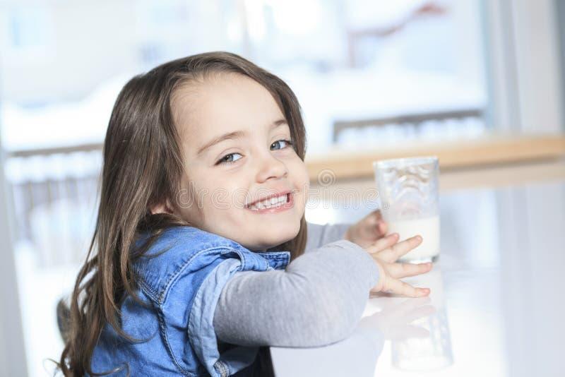 Leite bebendo feliz de criança pequena em uma cozinha imagens de stock royalty free