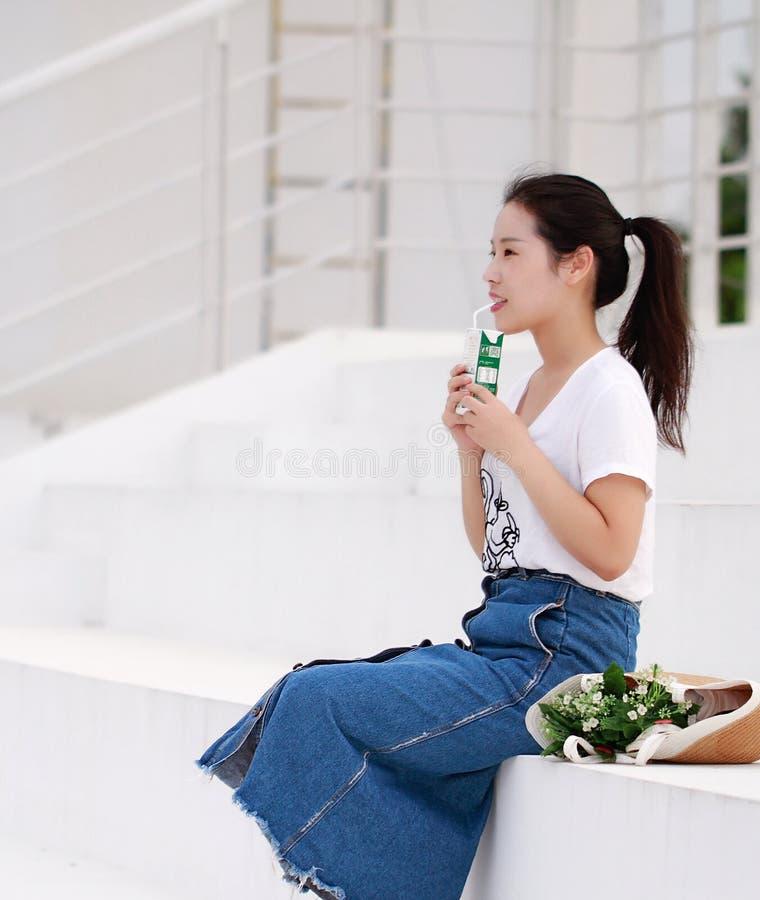 Leite chinês asiático da bebida da estudante universitário no campo de jogos foto de stock