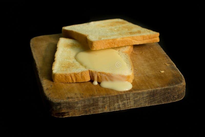Leite condensado e pães Sweetened fotografia de stock