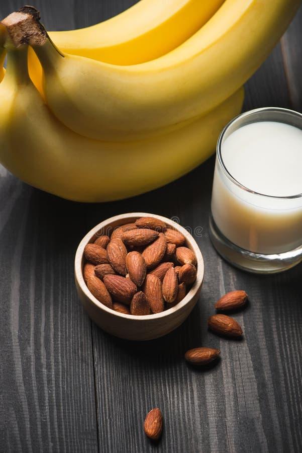 Leite da amêndoa em um vidro com porcas e bananas da amêndoa em uma tabela de madeira Alimento saudável e conceito da bebida imagem de stock royalty free