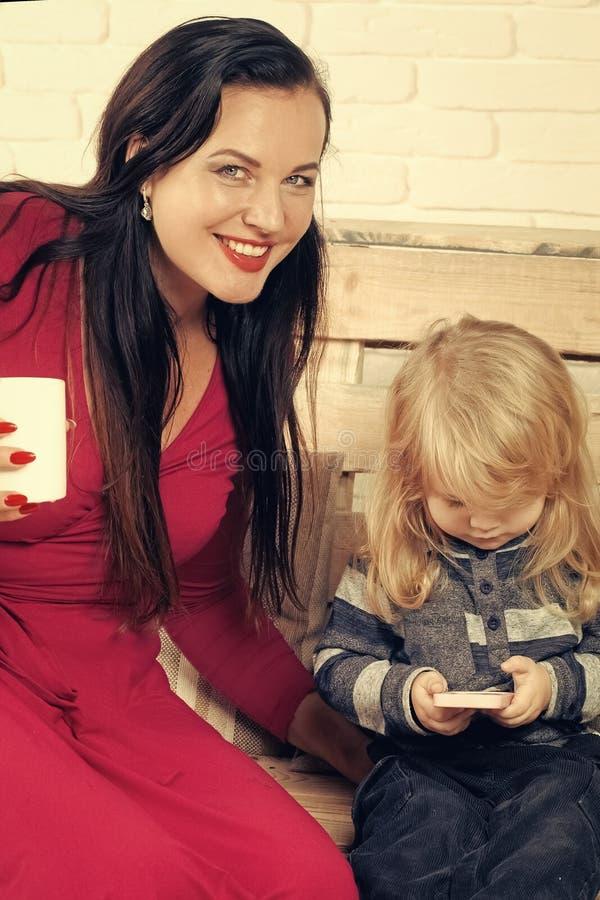 Leite da bebida da mulher e da criança Menino e menina pequenos no banco com telefone celular fotos de stock