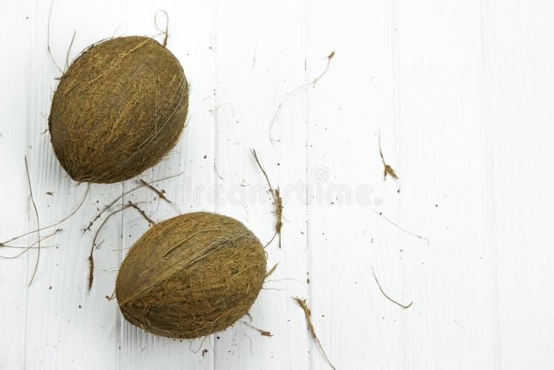 Leite de coco orgânico branco marrom tropical fresco da polpa de dois cocos no fundo branco de madeira fotografia de stock