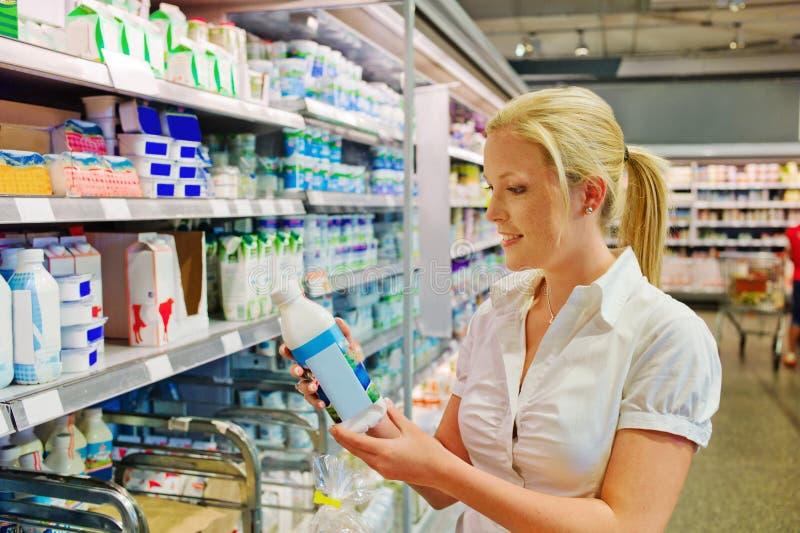 Leite de compra da mulher no mantimento foto de stock