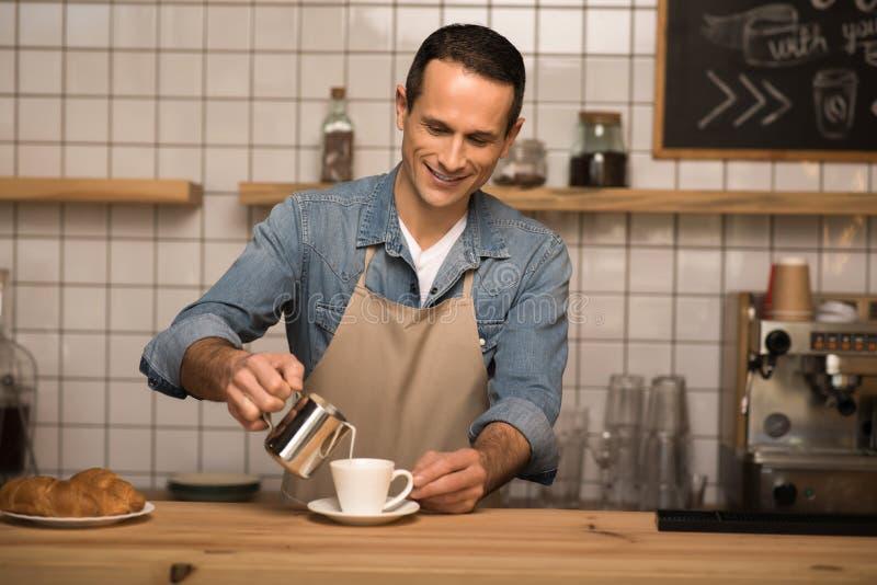 Leite de derramamento de Barista no café fotografia de stock royalty free