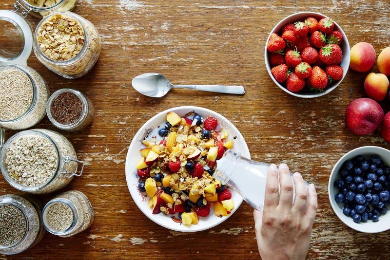 Leite de derramamento da mão da cena do café da manhã na nutrição orgânica do estilo de vida saudável do muesli foto de stock