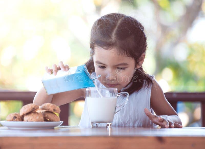 Leite de derramamento da menina asiática bonito da criança pequena no vidro foto de stock