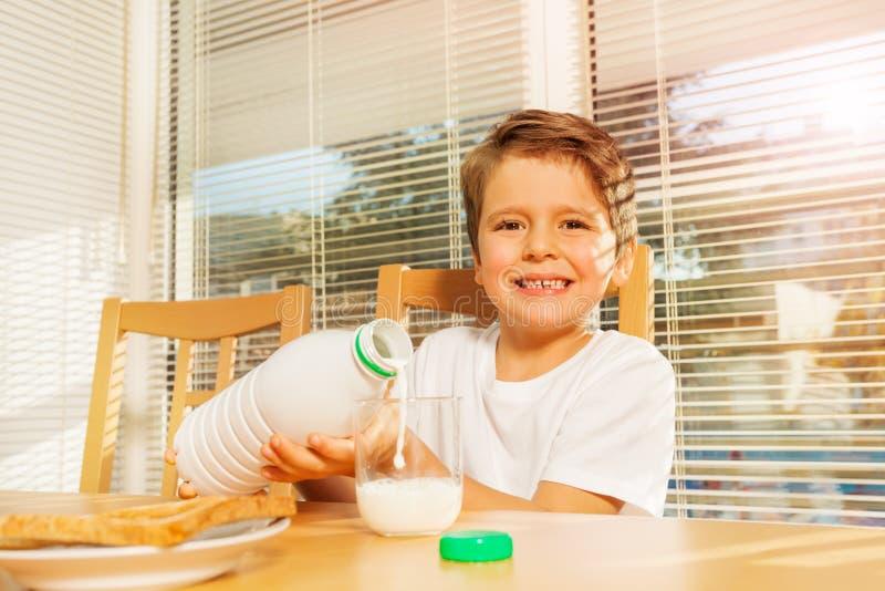 Leite de derramamento do menino feliz no café da manhã na cozinha fotos de stock