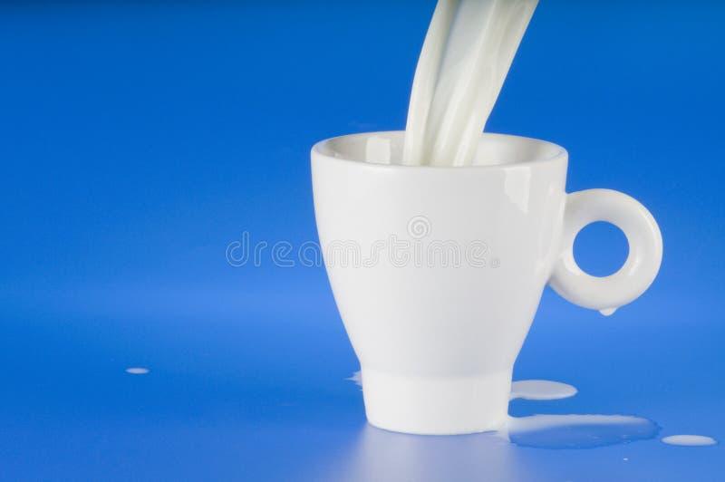 Leite de derramamento em um copo branco fotos de stock royalty free