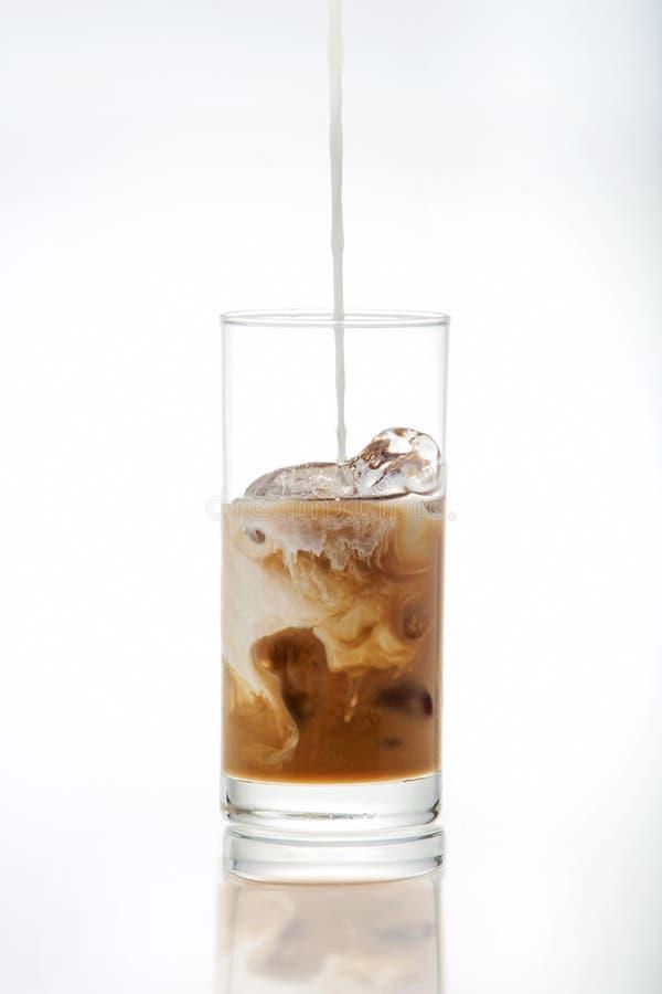 Leite de derramamento em um vidro do café de gelo fotografia de stock royalty free