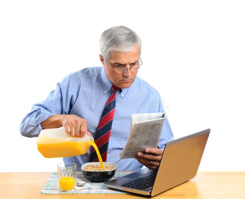 Leite de derramamento envelhecido médio do homem em sua bacia de cereal imagem de stock