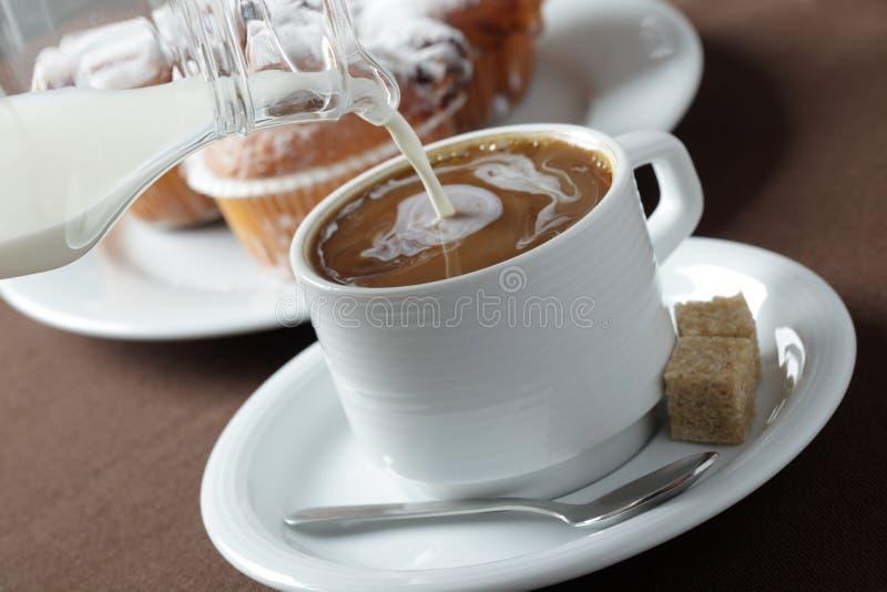 Leite de derramamento no café imagem de stock royalty free