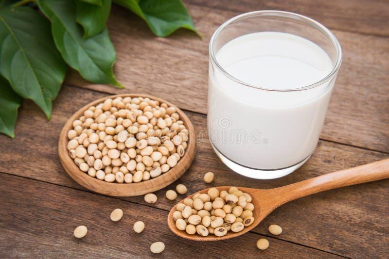 Leite de soja e feijão da soja no fundo de madeira foto de stock
