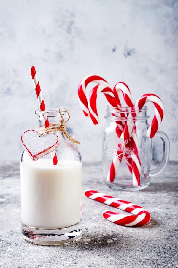 Leite do Natal para Santa na garrafa com o bastão de doces da palha e da pastilha de hortelã Bebida da festa natalícia do Natal fotos de stock royalty free