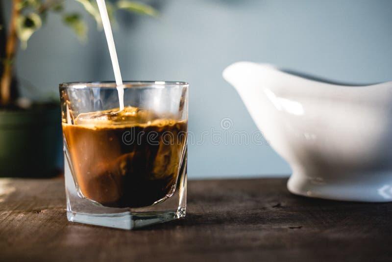Leite e café de derramamento em um vidro fotografia de stock royalty free