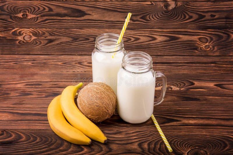 Leite e frutos em um fundo marrom Bananas deliciosas e um coco nutritivo Dois frascos de pedreiro com leite saboroso imagens de stock