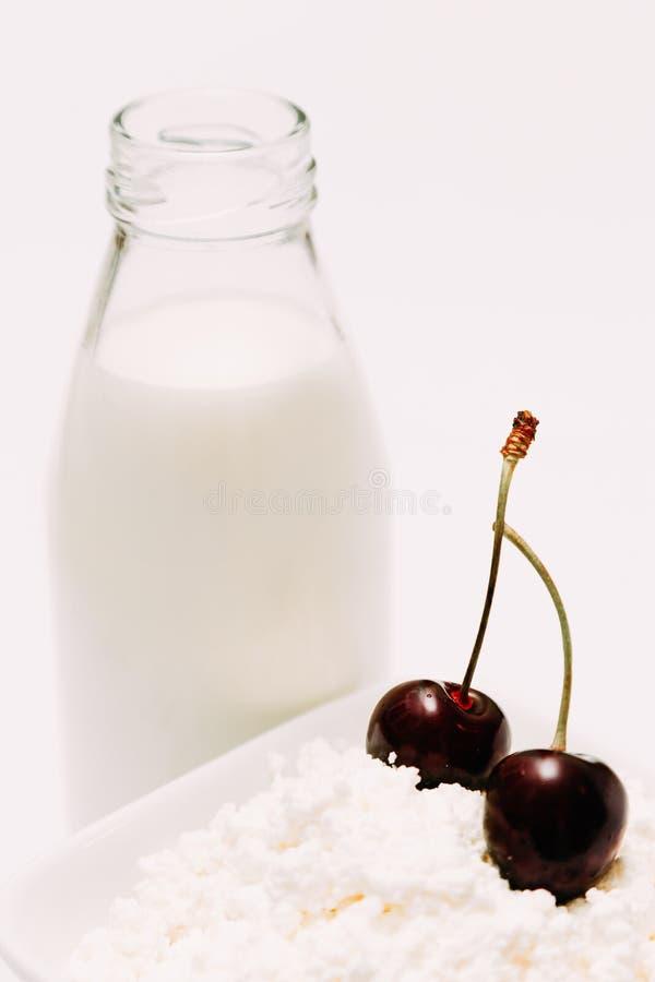 Leite em um requeijão da garrafa e em bagas da cereja em um fundo branco fotos de stock