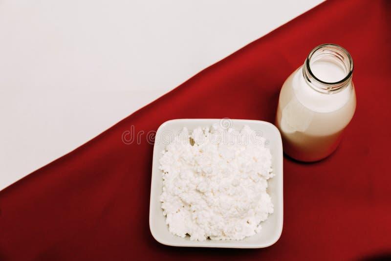 Leite em um requeijão da garrafa e em bagas da cereja em um fundo vermelho e branco fotos de stock
