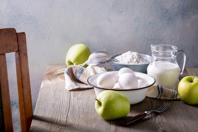 Leite, farinha, ovos e maçãs verdes numa mesa de madeira Ingredientes para charlotte de maçã foto de stock