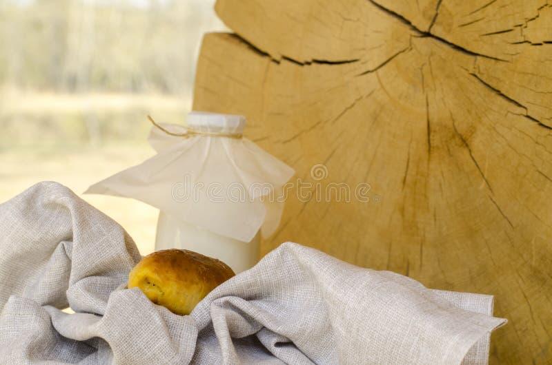Leite fresco em uma garrafa de vidro e em um vidro, ao lado das tortas em uma tabela de madeira O conceito de produtos org?nicos  imagem de stock royalty free