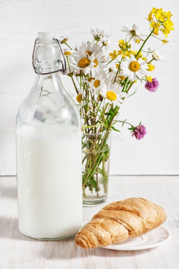 Leite fresco na garrafa antiquado com croissant imagens de stock