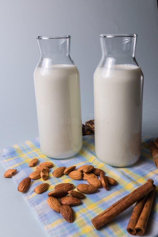 Leite natural do alkond em umas garrafas com porcas da amêndoa e varas de canela no guardanapo, sobre o fundo branco foto de stock